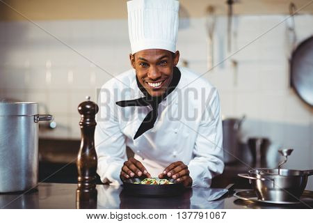 Portrait of smiling chef preparing a salad in commercial kitchen