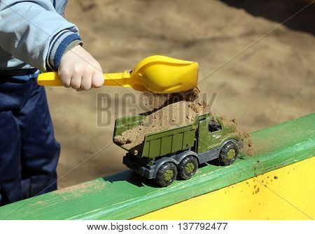 boy playing in sandbox. Sand and toys.
