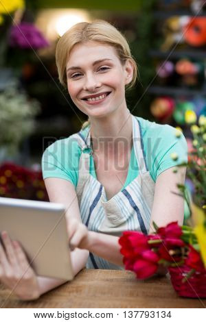 Portrait of happy female florist using digital tablet in florist shop