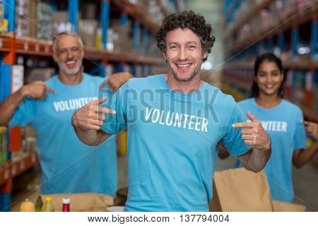 Focus of happy volunteer showing his tee-shirt in front of his team in a warehouse