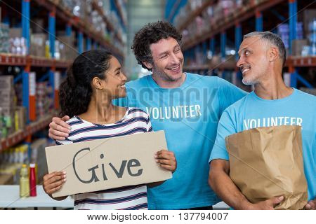 Happy volunteer are smiling and looking each other in a warehouse