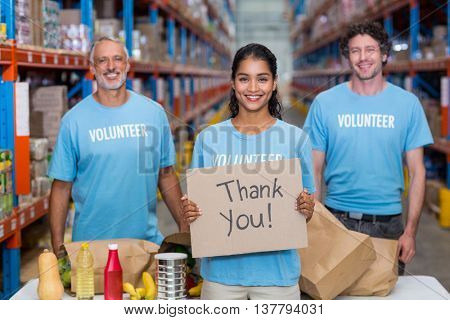 Happy volunteer holding a sign and posing with her team in a warehouse