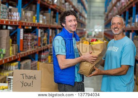 Happy volunteers holding a grocery bag and looking the camera in a warehouse