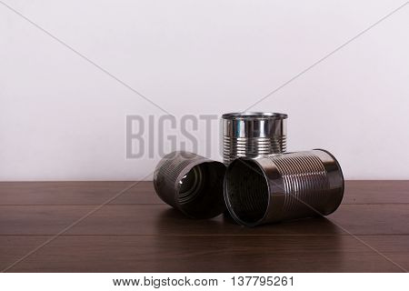 Battered Tin Cans On A Wooden Background