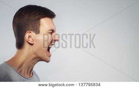 Close up face of man shouting with anger. Cry and stand in profile. Isolated on grey background. Copy space
