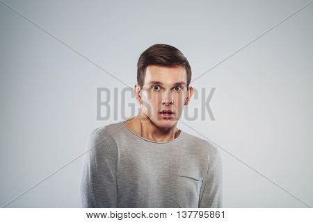 Terrible shocking news. Portrait of surprised, scared man and tie keeping mouth open and looking at camera while standing against grey background.