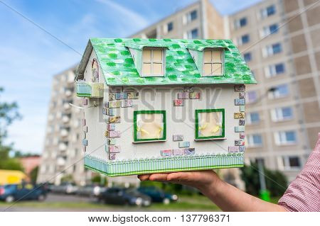 Real estate agent holding model house from paper on blurred background