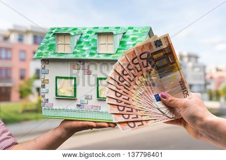 Real Estate Agent Holding Model House From Paper And New Propert