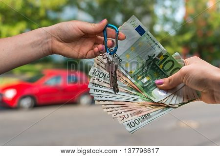 Salesman Giving Car Key To A New Car Owner, Who Is Paying By Eur