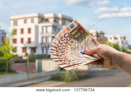 Property Buyer Holding Euro Banknotes And Buying Beautiful House