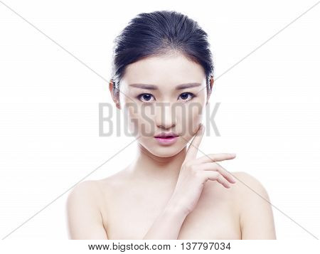 studio portrait of a young and beautiful asian woman hand on chin looking at camera isolated on white background.