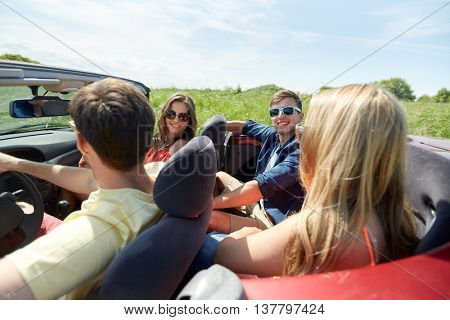 leisure, road trip, travel and people concept - happy friends driving in cabriolet car along country road and talking
