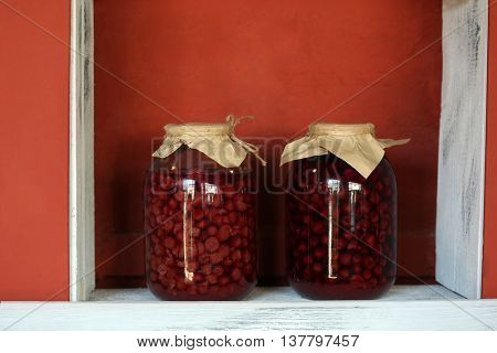 Preserved cherries in glass jar on white wooden shelf