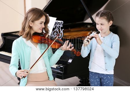 Two girls playing violin and flute on piano background