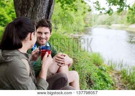 travel, tourism, hike, camping and people concept - happy couple with cups drinking tea in nature on river bank