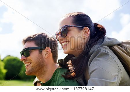 travel, hiking, backpacking, tourism and people concept - happy couple in sunglasses with backpacks having fun and hugging outdoors