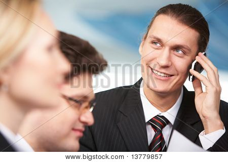 Photo of handsome employer calling his partner with colleagues near by
