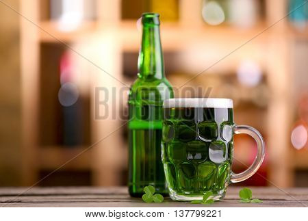 Glass of green beer with clover leaves and bottle on blurred bar background