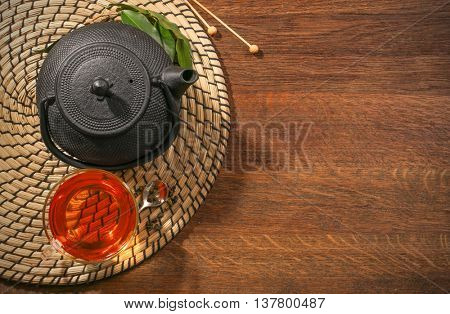 Traditional eastern teapot and teacup on wooden desk