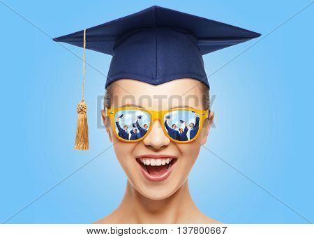 graduation, education, school and people concept - happy screaming teenage girl in shades and mortarboard or bachelor hat over blue background