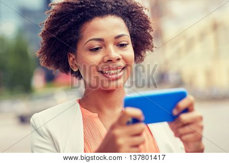 business, technology, communication and people concept - young smiling african american businesswoman with smartphone reading message on city street
