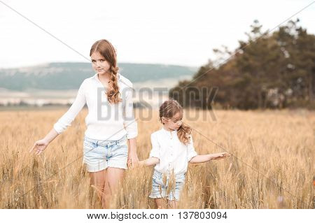 Two sisters in similar clothes walking in rye field outdoors. Togetherness. Friendship.