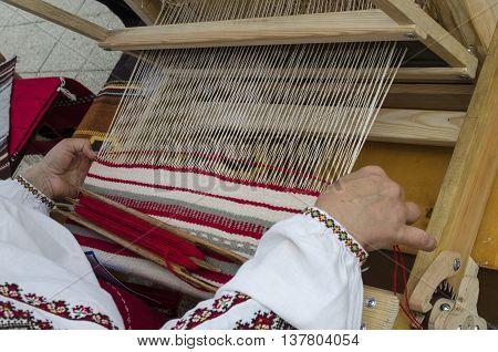 woman knits Ukrainian folk towel on the loom outdoors