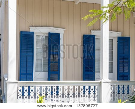 Blue Shutters on Tropical Veranda of yellow home