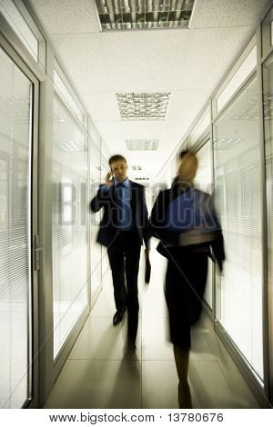 Portrait of business people walking down long corridor in office building