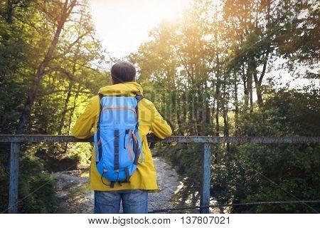 Tourist man on the old bridge over mountain river