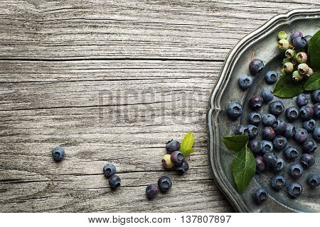 Juicy and fresh blueberries with green leaves on rustic table