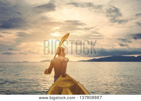 a guy pulling kayak to the sea in sunset, vacation holiday summertime concepts, vintage tone