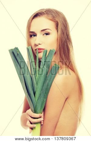 Topless caucasian woman holding green fresh leek.