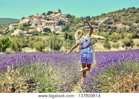 Young woman raised her hands up in lavender. Young woman walking in purple lavender flowers. On the background of green trees and blue sky.