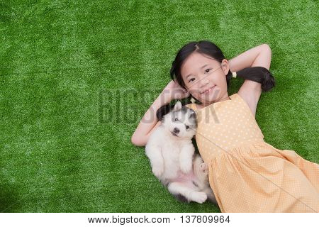 Cute asian girl lying with her puppy on green grass
