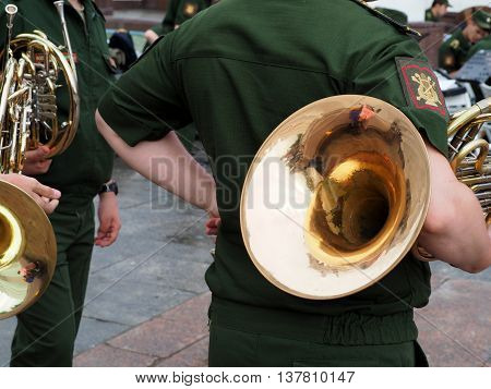 Standing back horn player with his French horn under his arm