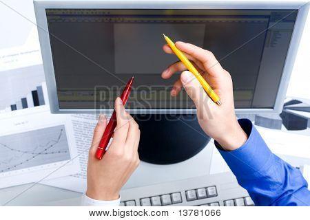 Foto de mãos masculinas e femininas com canetas do monitor durante discussão