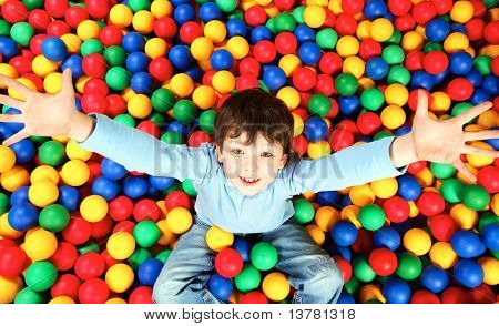 Feliz muchacho sentado en bolas coloridas y estirar los brazos para cámara