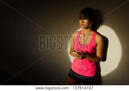 Urban Sporty Woman Listening Music On Smartphone