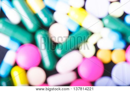 Blurry pharmacy background on a black table. Tablets on a black background. Pills. Medicine and healthy. Close up of capsules. Differend kind of pills