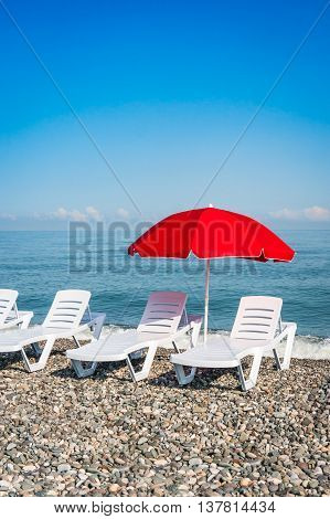 Beach Chairs And Red Umbrella On Shingle Beach