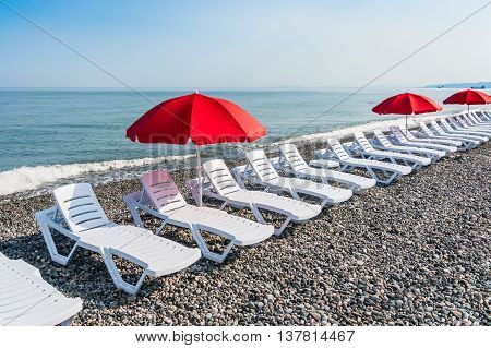 Beach Chairs Or Beds And Sun Red Umbrellas On The Beach