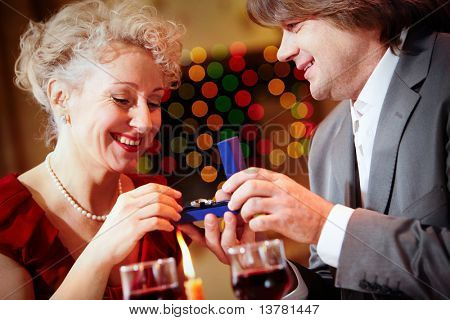 Image of handsome man making proposal to beautiful woman while holding small open box before her