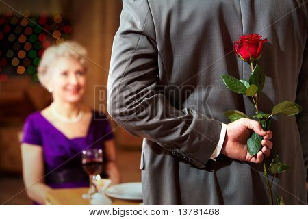 Rear view of man holding red rose in hand on background of intrigued female