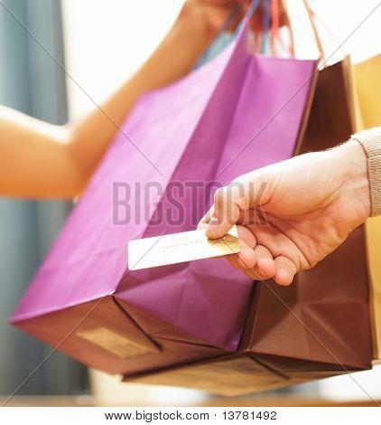 Vertikale Bild des Mannes? s Hand übergeben über Kreditkarte Verkäuferin nach dem Einkaufen