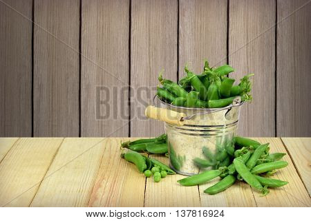 Metal bucket full of pods of green peas on a wooden background. Open the pod and peas. Summer. The season of harvest. Agriculture pastime.