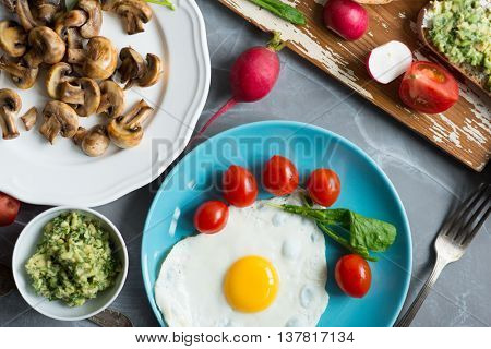 Fried eggs sunny side up served on blue plate with vegetables and fresh bread