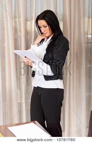 Serious Executive Woman Reading In Office