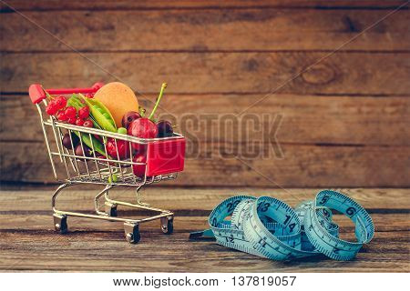Shopping cart with fruits, berries, tape line on old wood background. Toned image.