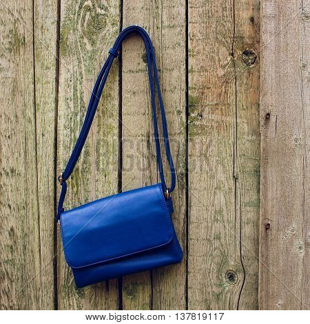 Blue women's handbag hanging on nail on old wooden background